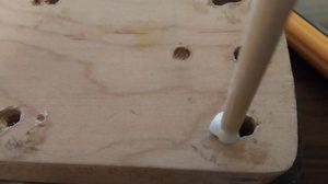 ギターのネックのビス穴に木の棒をねじ込んで埋めていく